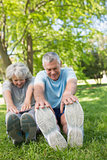 Mature couple stretching hands to legs at park