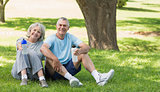 Smiling mature couple sitting with water bottles at park