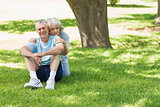 Mature couple sitting on grass at park