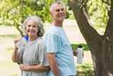 Smiling mature couple with water bottles at park