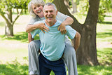 Cheerful mature man carrying woman at park