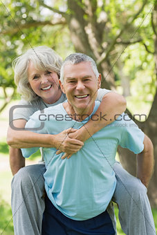 Happy mature man carrying woman at park
