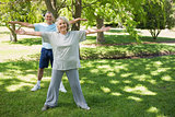 Portrait of mature couple stretching hands at park