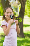 Smiling girl holding leaves and magnifying glass at park