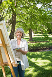Smiling mature woman painting on canvas in park