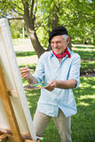 Happy mature man painting in park