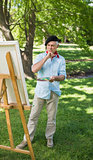 Full length of a mature man painting in park