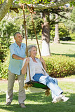 Mature couple at swing in park