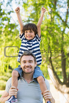 Father carrying a happy son on shoulders at park