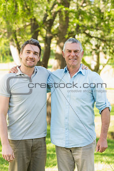 Smiling father with adult son at park