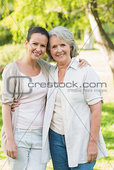 Portrait of smiling woman with adult daughter at park