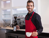 Handsome young barista holding jug and cup of coffee