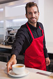 Smiling young barista putting cup of coffee down on counter