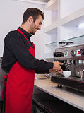 Happy young barista making cup of coffee
