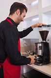Happy barista grinding coffee beans