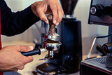 Barista pressing fresh coffee grounds
