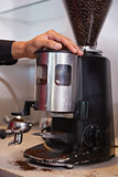 Barista using coffee grinder to grind beans