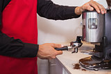 Barista using coffee grinder to grind coffee beans