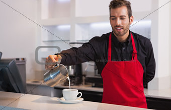 Smiling barista pouring milk into cup of coffee