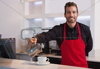 Smiling barista pouring milk into cup of coffee looking at camera