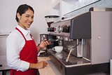 Pretty barista making coffee smiling at camera