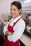 Pretty young barista leaning against counter smiling at camera