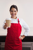 Pretty young barista offering cup of coffee to go
