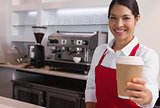 Happy young barista offering cup of coffee to go smiling at camera
