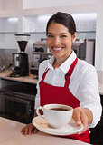 Pretty young barista offering cup of coffee smiling at camera