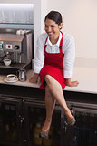 Pretty barista sitting on counter and smiling