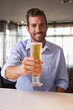 Happy businessman raising glass of beer to camera after work
