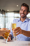Happy businessman clinking glass of beer with bartender
