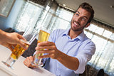 Smiling businessman clinking glass of beer with bartender