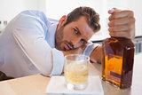 Drunk businessman clutching whiskey bottle looking at camera
