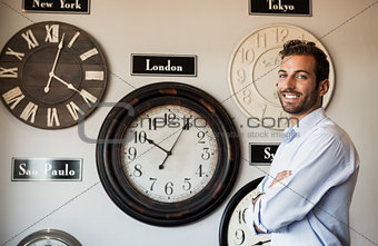 Happy businessman standing beside wall of international clocks