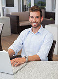 Smiling businessman working on laptop at table