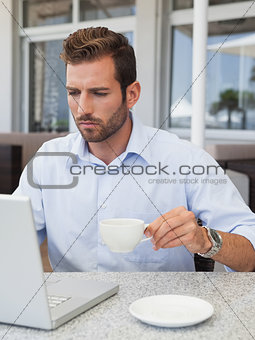 Concentrating businessman working with laptop at table