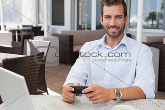 Happy businessman sending a text at table