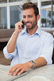 Happy businessman talking on phone using his laptop