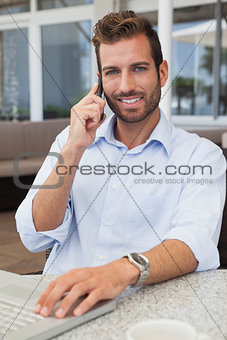 Smiling businessman talking on phone using his laptop