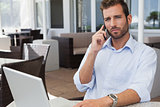 Frowning businessman talking on phone using his laptop