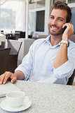 Smiling young businessman talking on phone using his laptop