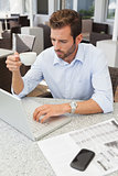 Frowning young businessman using his laptop holding coffee cup