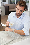 Frowning young businessman checking time holding coffee cup