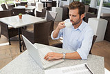 Frowning young businessman working at laptop drinking coffee