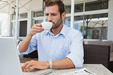 Serious young businessman working at laptop drinking coffee