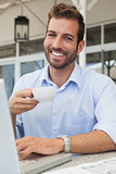 Happy young businessman working at laptop drinking coffee