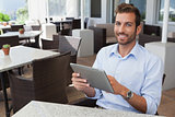 Happy young businessman working on tablet
