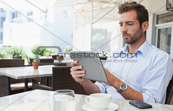 Focused young businessman working on tablet
