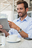 Cheerful young businessman working on tablet